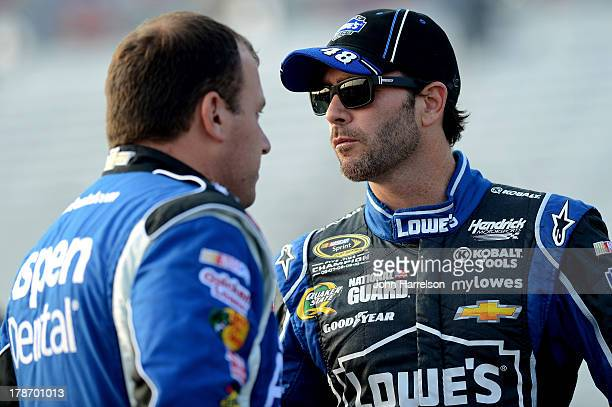Jimmie Johnson driver of the Lowe's Dover White Chevrolet talks with Ryan Newman driver of the Aspen Dental Chevrole during qualifying for the NASCAR...