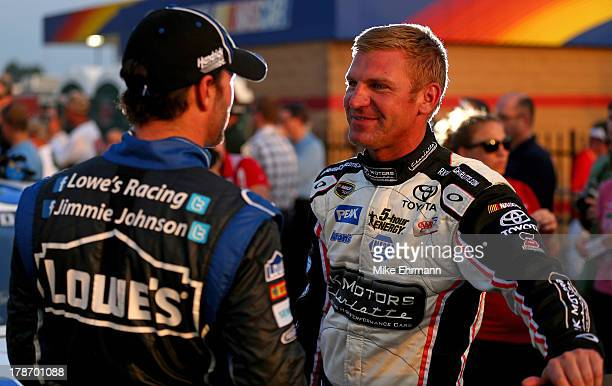 Jimmie Johnson driver of the Lowe's Dover White Chevrolet talks with Clint Bowyer driver of the RKMotorsCharlottecom Toyota during qualifying for the...