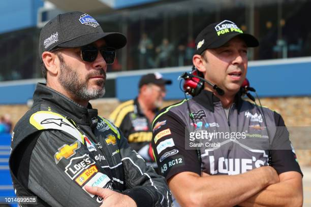 Jimmie Johnson driver of the Lowe's for Pros Chevrolet and crew chief Chad Knaus stand on the grid during qualifying for the Monster Energy NASCAR...