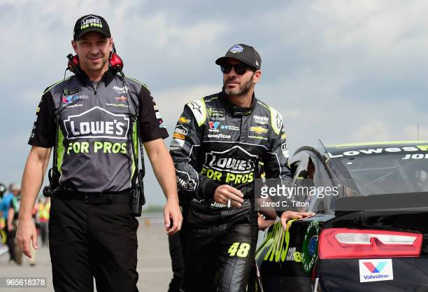 Jimmie Johnson driver of the Lowe's for Pros Chevrolet and crew chief Chad Knaus walk on the grid during qualifying for the Monster Energy NASCAR Cup...
