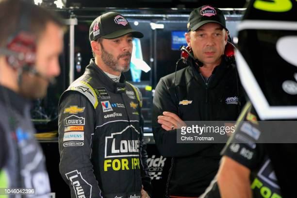 Jimmie Johnson driver of the Lowe's for Pros Chevrolet and his crew chief Chad Knaus stand in the garage area during practice for the Monster Energy...