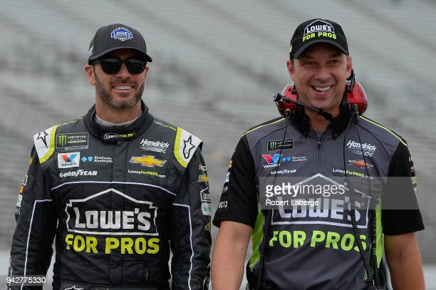 Jimmie Johnson driver of the Lowe's for Pros Chevrolet walks on the grid with crew chief Chad Knaus during qualifying for the Monster Energy NASCAR...