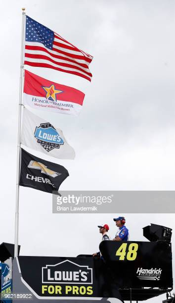 Jimmie Johnson driver of the Lowe's Patriotic Chevrolet and his crew chief Chad Knaus look on from the top of the team hauler during practice for the...