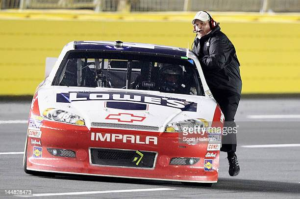 Jimmie Johnson driver of the Lowe's Patriotic Chevrolet celebrates by doing a victory lap with team owner Rick Hendrick sitting on the door after...