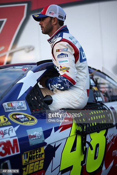 Jimmie Johnson driver of the Lowe's Patriotic Chevrolet climbs into his car during qualifying for the NASCAR Sprint Cup Series Sprint AllStar Race at...