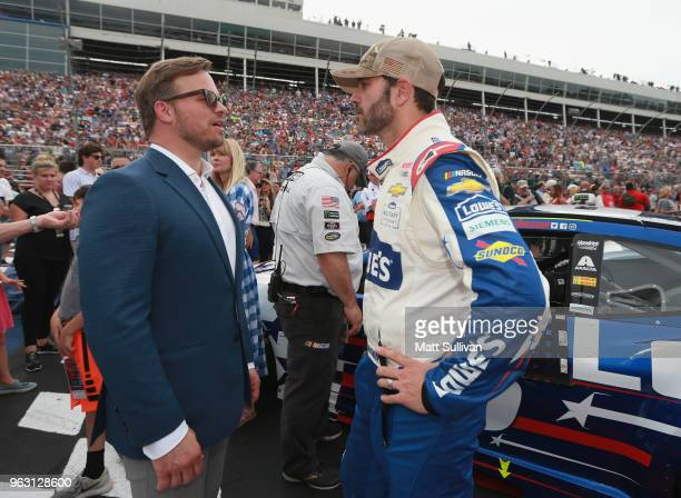 Jimmie Johnson driver of the Lowe's Patriotic Chevrolet speaks with president of Charlotte Motor Speedway Marcus Smith during prerace ceremonies for...