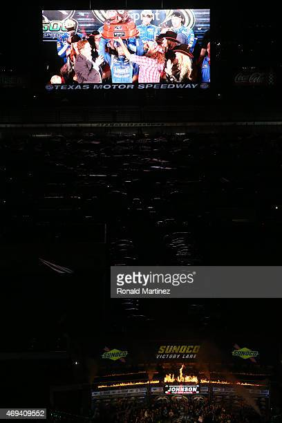 Jimmie Johnson, driver of the Lowe's Pro Services Chevrolet, is seen raising the winner's trophy in Victory Lane on the Big Hoss screen following his...