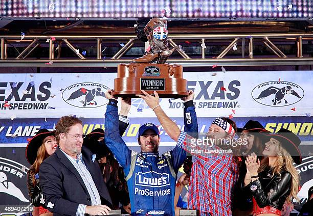 Jimmie Johnson driver of the Lowe's Pro Services Chevrolet raises the winners trophy in Victory Lane after winning the NASCAR Sprint Cup Series Duck...