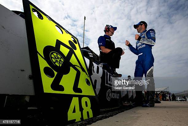Jimmie Johnson driver of the Lowe's Pro Services Chevrolet right talks with crew chief Chad Knaus on the grid during qualifying for the NASCAR Sprint...