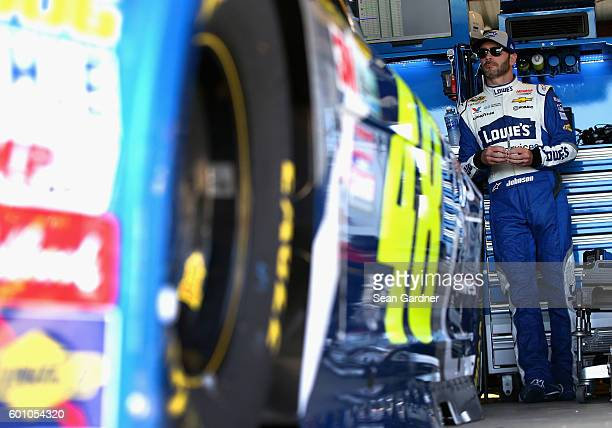 Jimmie Johnson driver of the Lowe's Pro Services Chevrolet stands in the garage area during practice for the NASCAR Sprint Cup Series Federated Auto...