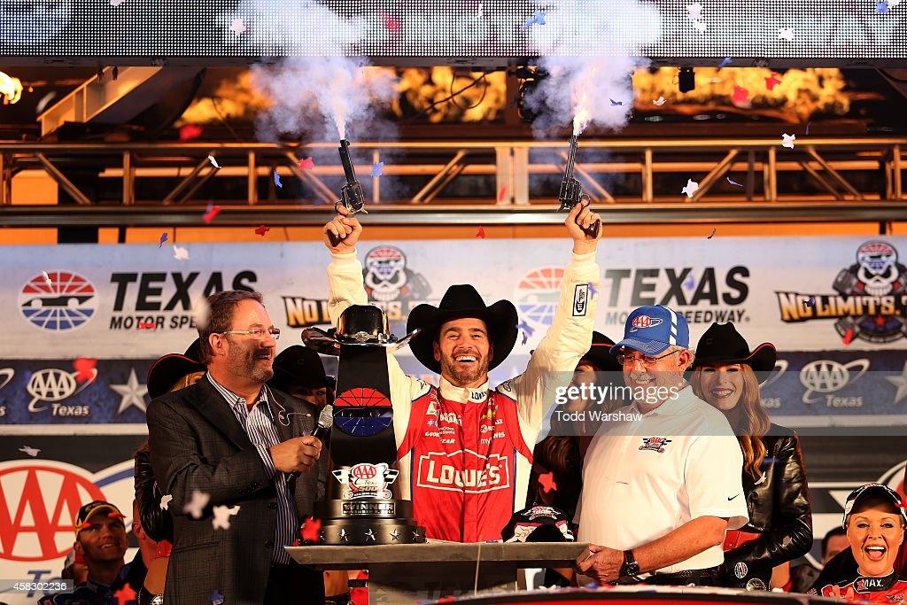 Jimmie Johnson, driver of the #48 Lowe's Red Vest Chevrolet, celebrates with pistols, Texas Motor Speedway President Eddie Gossage and AAA VIP Employee Recognition Winner David Tiger in Victory Lane after winning the NASCAR Sprint Cup Series AAA Texas 500 at Texas Motor Speedway on November 2, 2014 in Fort Worth, Texas.