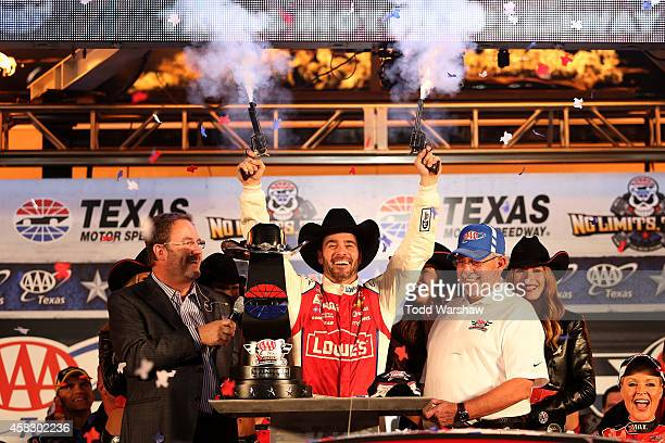 Jimmie Johnson driver of the Lowe's Red Vest Chevrolet celebrates with pistols Texas Motor Speedway President Eddie Gossage and AAA VIP Employee...