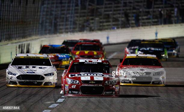 Jimmie Johnson, driver of the Lowe's Red Vest Chevrolet, races ahead of Brad Keselowski, driver of the Miller Lite Ford, and Kevin Harvick, driver of...