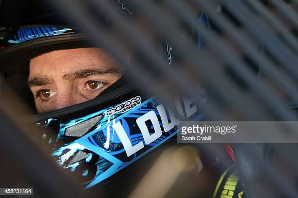 Jimmie Johnson, driver of the Lowe's Red Vest Chevrolet, sits in his car in the garage area during practice for the NASCAR Sprint Cup Series AAA...