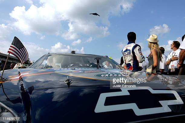 Jimmie Johnson driver of the Lowe's Summer Salute Chevrolet stands on the grid with his wife Chandra as a B2 Spirit flys over prior to the NASCAR...