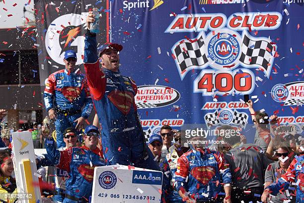 Jimmie Johnson, driver of the Lowe's / Superman Chevrolet, celebrates in victory lane after winning the NASCAR Sprint Cup Series Auto Club 400 at...
