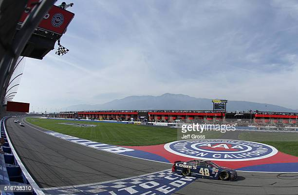 Jimmie Johnson, driver of the Lowe's / Superman Chevrolet, takes the checkered flag to win the NASCAR Sprint Cup Series Auto Club 400 at Auto Club...