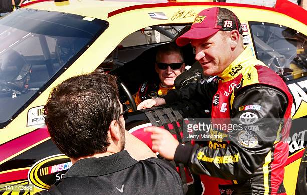 Jimmie Johnson driver of the Lowe's/Jimmie Johnson Foundation Chevrolet talks with Clint Bowyer driver of the 5hour Energy Toyota and Jeff Burton...