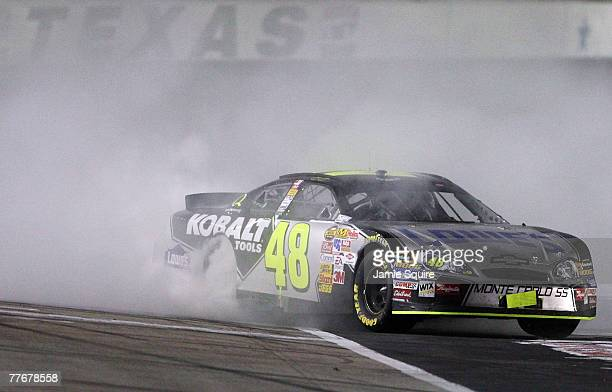 Jimmie Johnson driver of the Lowe's/Kobalt Chevrolet celebrates by burning out his tires after winning the NASCAR Nextel Cup Series Dickies 500 at...