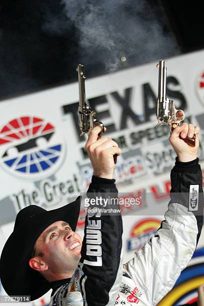 Jimmie Johnson driver of the Lowe's/Kobalt Chevrolet celebrates in victory lane by firing guns in the air after winning the NASCAR Nextel Cup Series...