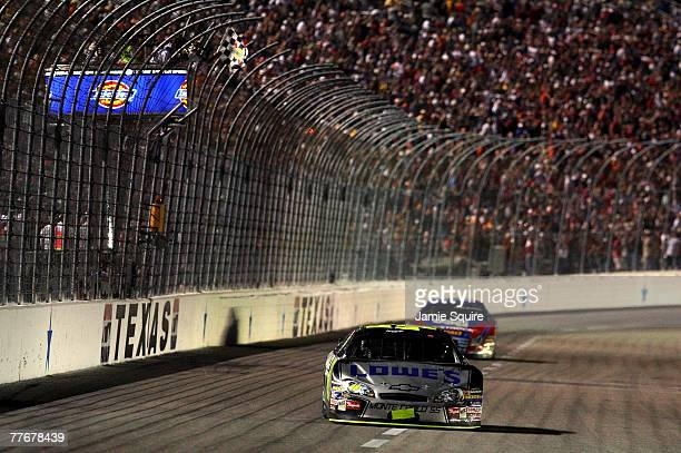 Jimmie Johnson driver of the Lowe's/Kobalt Chevrolet crosses the finish line ahead of Matt Kenseth driver of the USG Ford to win the NASCAR Nextel...