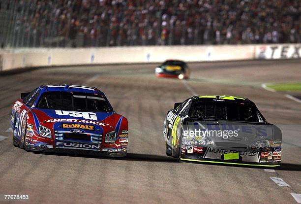 Jimmie Johnson driver of the Lowe's/Kobalt Chevrolet races Matt Kenseth driver of the USG Ford side by side during the NASCAR Nextel Cup Series...