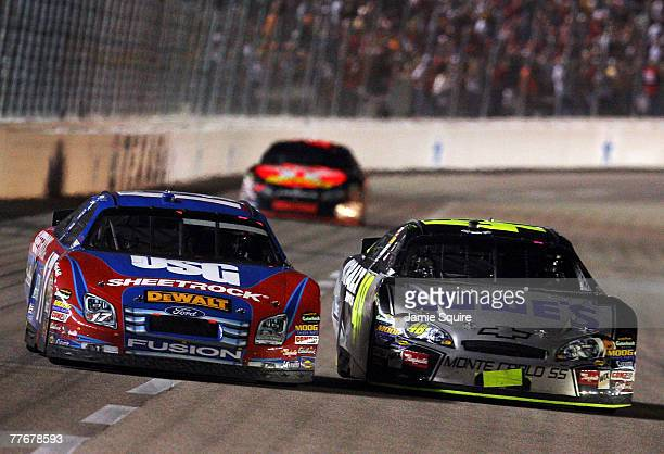 Jimmie Johnson driver of the Lowe's/Kobalt Chevrolet races Matt Kenseth driver of the USG Ford side by side as they pass Juan Pablo Montoya driver of...