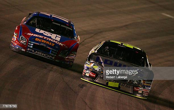 Jimmie Johnson driver of the Lowe's/Kobalt Chevrolet races next to Matt Kenseth driver of the USG Ford during the NASCAR Nextel Cup Series Dickies...