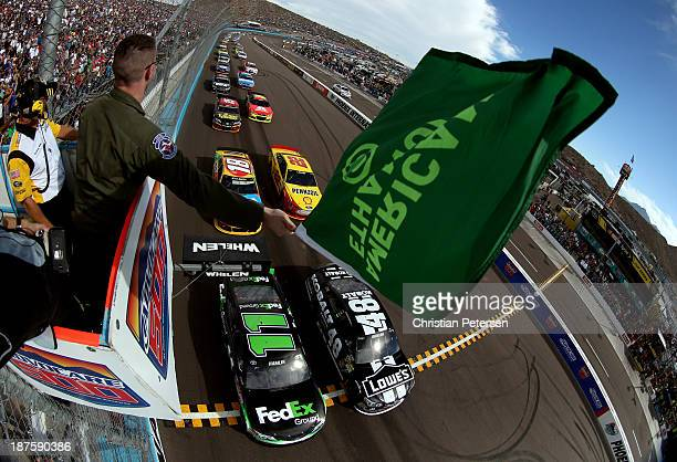 Jimmie Johnson driver of the Lowe's/Kobalt Tools Chevrolet and Denny Hamlin driver of the FedEx Ground Toyota lead the field at the start of the...