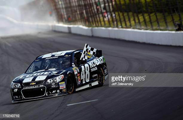 Jimmie Johnson driver of the Lowe's/Kobalt Tools Chevrolet celebrates with the checkered flag after winning the NASCAR Sprint Cup Series Party in the...