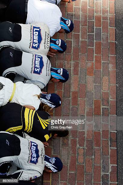 Jimmie Johnson driver of the Lowe's/KOBALT Tools Chevrolet celebrates by kissing the bricks after Johnson wins the NASCAR Sprint Cup Series Allstate...