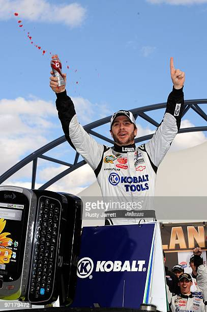 Jimmie Johnson driver of the Lowe's/Kobalt Tools Chevrolet celebrates in Victory Lane after winning the NASCAR Sprint Cup Series Shelby American at...