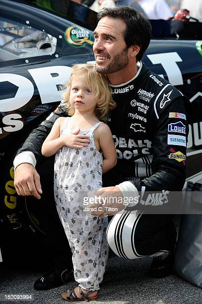 Jimmie Johnson driver of the Lowe's/Kobalt Tools Chevrolet stands with his daughter Genevieve prior to the NASCAR Sprint Cup Series GEICO 400 at...