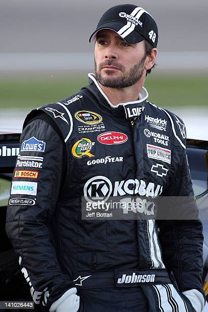 Jimmie Johnson driver of the Lowe's/Kobalt Tools Chevrolet waits by his car during qualifying for the NASCAR Sprint Cup Series Kobalt Tools 400 at...