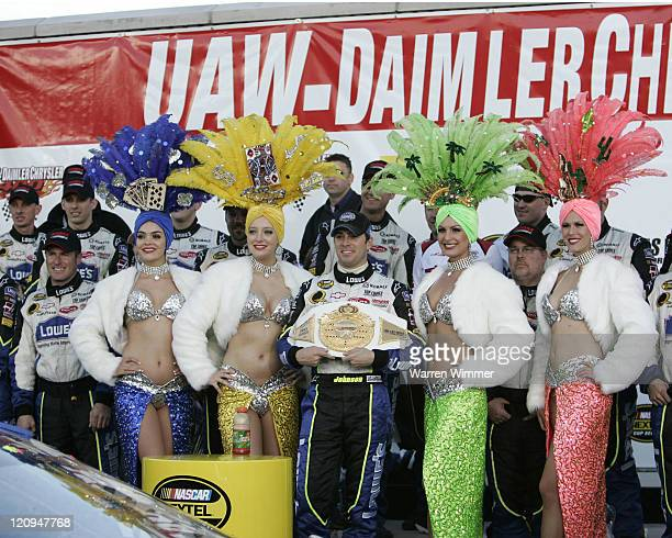 Jimmie Johnson flanked by Vegas Show Girls celebrate his victory at the Las Vegas Motor Speedway Jimmie Johnson won the race for the second year in a...