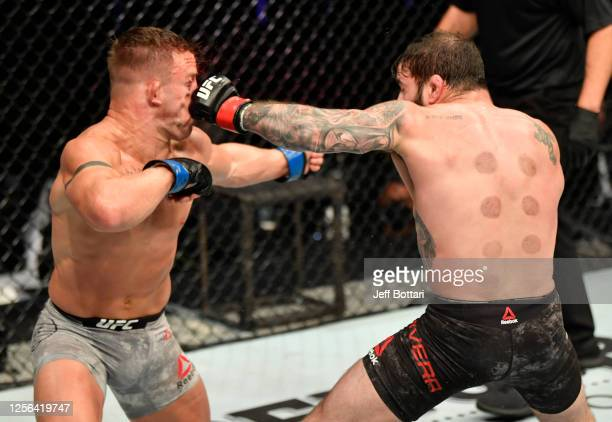 Jimmie Rivera punches Cody Stamann in their featherweight fight during the UFC Fight Night event inside Flash Forum on UFC Fight Island on July 16,...