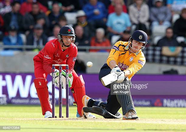 Jimmy Adams of Hampshire hits out with Jos Buttler of Lancashire Lightning looking on during the Natwest T20 Blast Semi Final match between Hampshire...