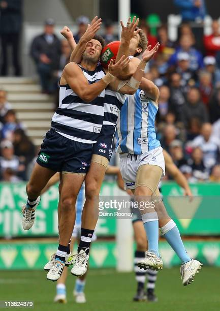 Jimmy Bartel and Tom Hawkins of the Cats attempt to mark during the round seven AFL match between the Geelong Cats and the North Melbourne Kangaroos...
