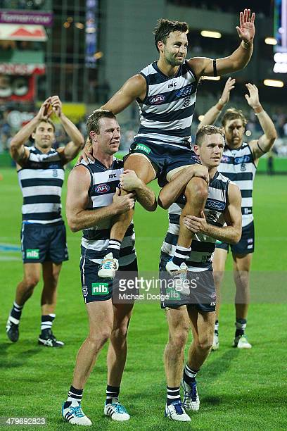 Jimmy Bartel of the Cats gets carried off by Steve Johnson and Joel Selwood after winning his 250th game during the round one AFL match between the...