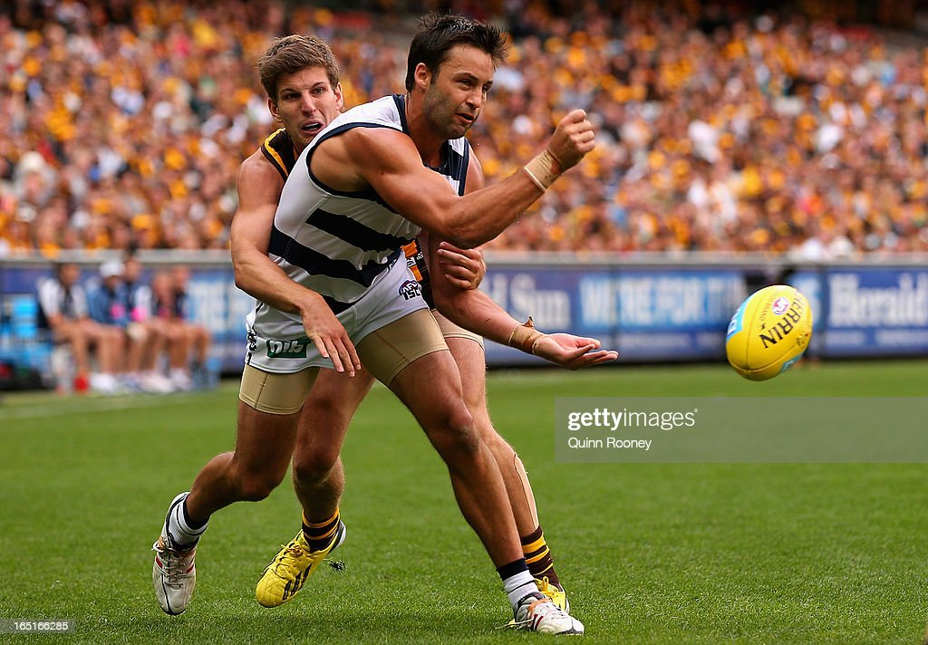 Jimmy Bartel of the Cats handballs whilst being tackled by Luke Breust of the Hawks during the round one AFL match between the Hawthorn Hawks and the Geelong Cats at the Melbourne Cricket Ground on April 1, 2013 in Melbourne, Australia.