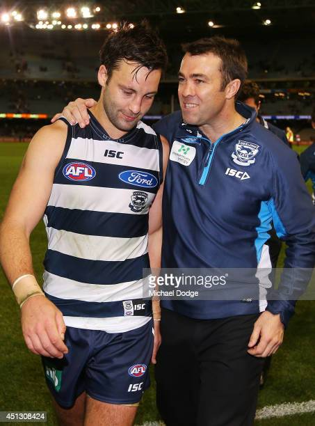 Jimmy Bartel of the Cats is hugged by coach Chris Scott after their win during the round 15 AFL match between the Geelong Cats and the Essendon...