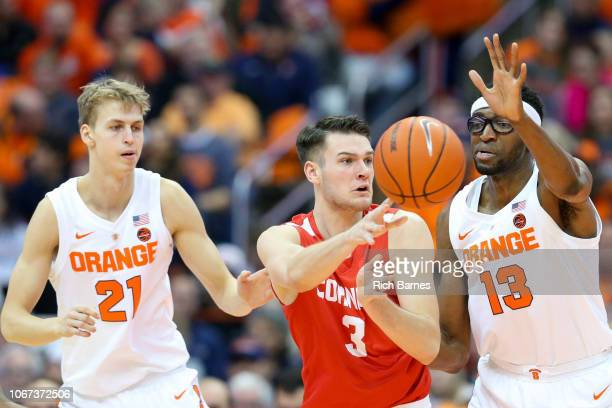 Jimmy Boeheim of the Cornell Big Red passes the ball between the defense of Marek Dolezaj and Paschal Chukwu of the Syracuse Orange during the second...