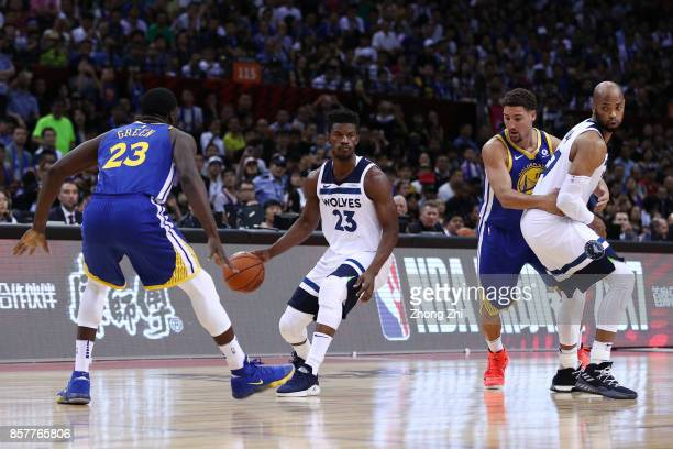 Jimmy Butler and Taj Gibson of the Minnesota Timberwolves in action against Klay Thompson and Draymond Green of the Golden State Warriors during the...