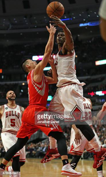 Jimmy Butler of the Chicago Bulls blocks a shot by Jeremy Lin of the Houston Rockets at the United Center on March 13 2014 in Chicago Illinois NOTE...