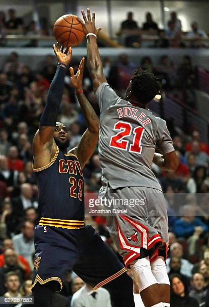 Jimmy Butler of the Chicago Bulls blocks a shot by LeBron James of the Cleveland Cavaliers at the United Center on December 2 2016 in Chicago Illinois