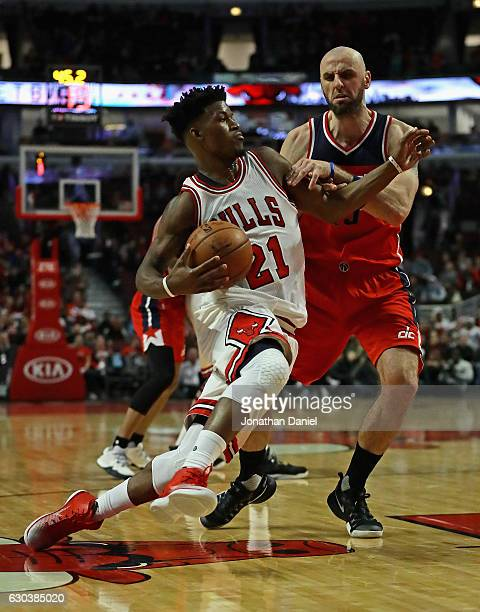 Jimmy Butler of the Chicago Bulls drives against Marcin Gortat of the Washington Wizards at the United Center on December 21 2016 in Chicago Illinois...