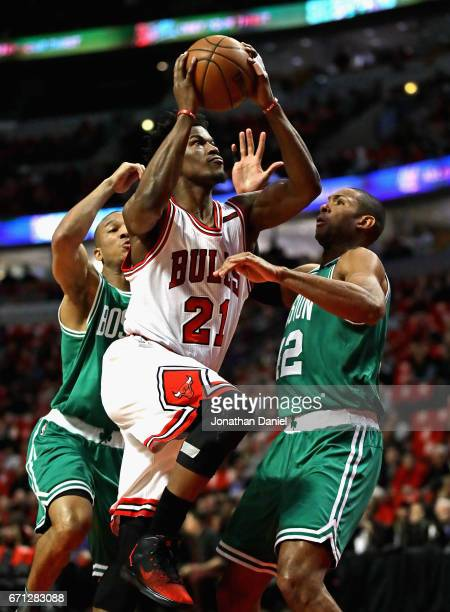 Jimmy Butler of the Chicago Bulls drives between Avery Bradley and Al Horford of the Boston Celtics during Game Three of the Eastern Conference...