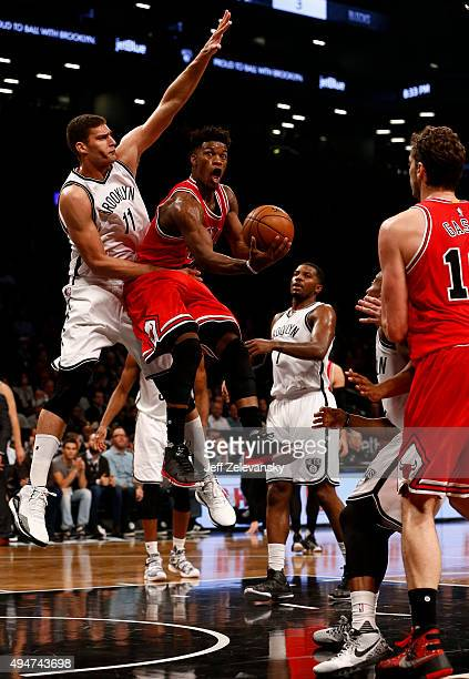 Jimmy Butler of the Chicago Bulls drives into Brook Lopez of the Brooklyn Nets during a game at Barclays Center on October 28 2015 in the Brooklyn...