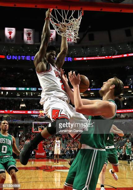 Jimmy Butler of the Chicago Bulls dunks over Kelly Olynyk of the Boston Celtics during Game Three of the Eastern Conference Quarterfinals during the...