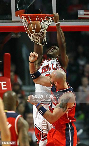 Jimmy Butler of the Chicago Bulls dunks over Marcin Gortat of the Washington Wizards at the United Center on December 21 2016 in Chicago Illinois